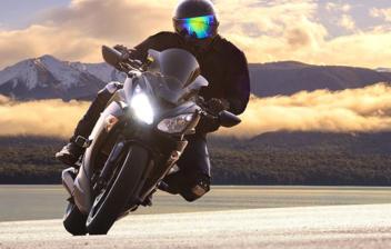 Motorista con traje negro tomando una curva con su motocicleta