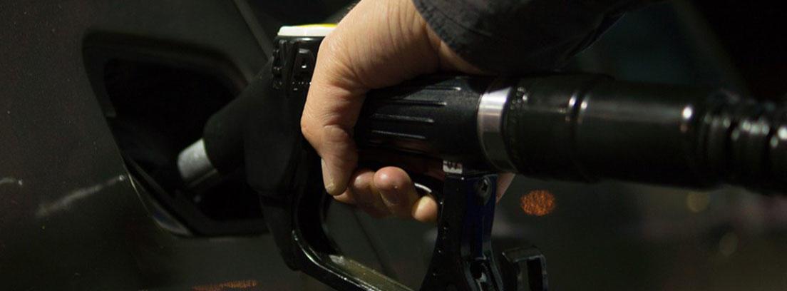 Persona con una manguera en la mano metiendo gasolina en un coche gris