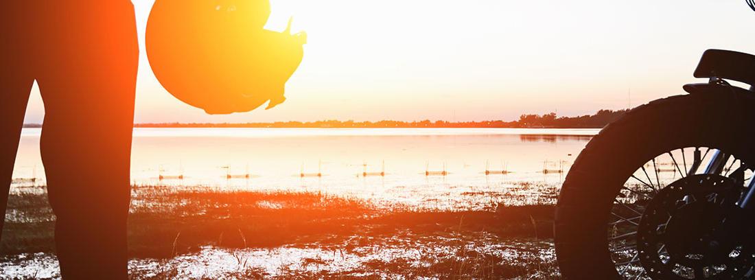 Un hombre con casco en mano al lado de su moto con el sol y un lago de fondo