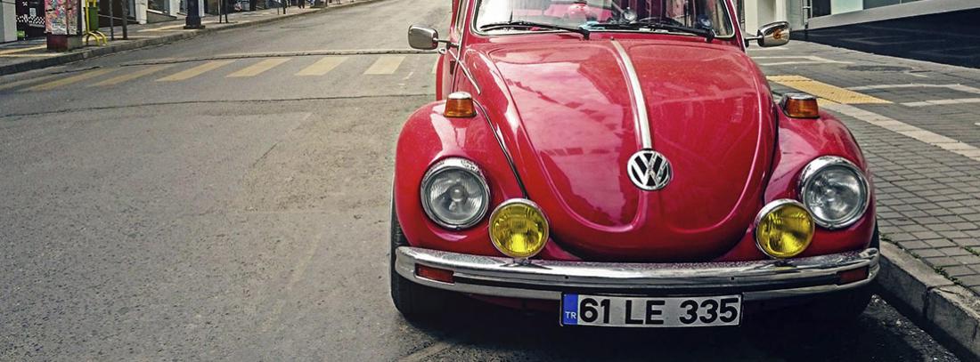 Coche rojo modelo Volkswagen escarabajo aparcado junto una acera.