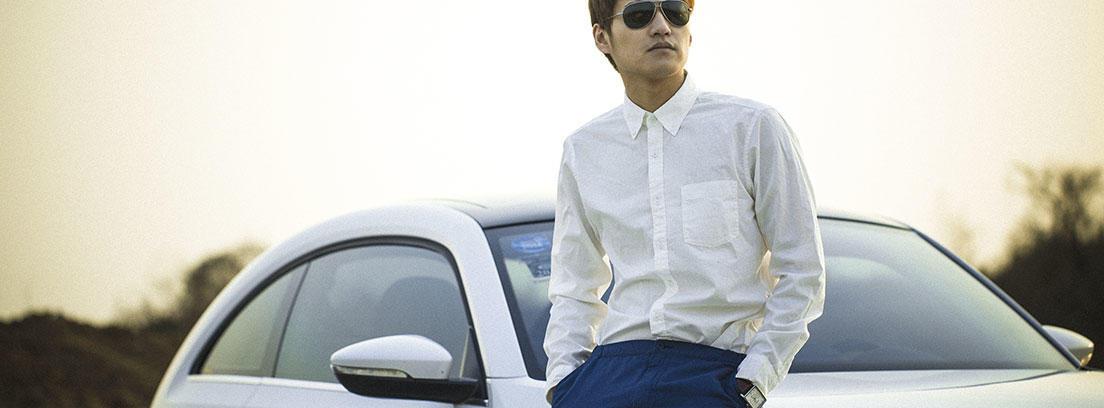 Hombre con gafas de sol y camisa blanca apoyado coche blanco Volkswagen escarabajo.