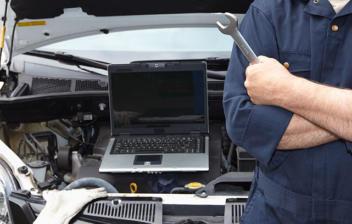 Mecánico observando el interior del coche con ayuda de un ordenador