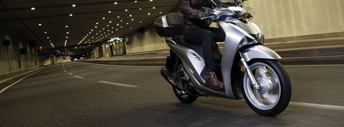 Hombre sobre una moto scooter Honda SH 125i gris en un tunel