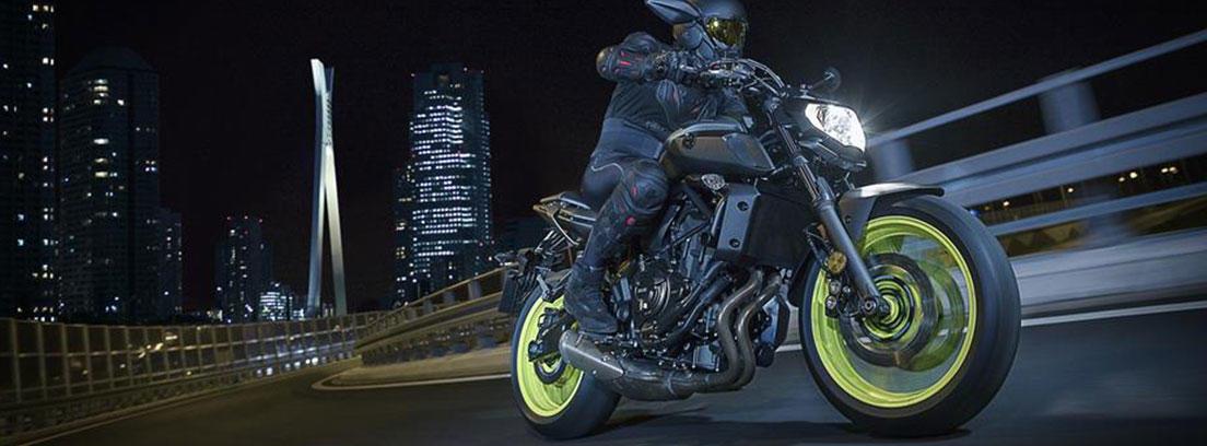 Moto Yamaha MT-07 oscura circulando en una ciudad de noche