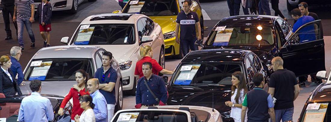 Dos filas de coches con carteles y personas entre ellos