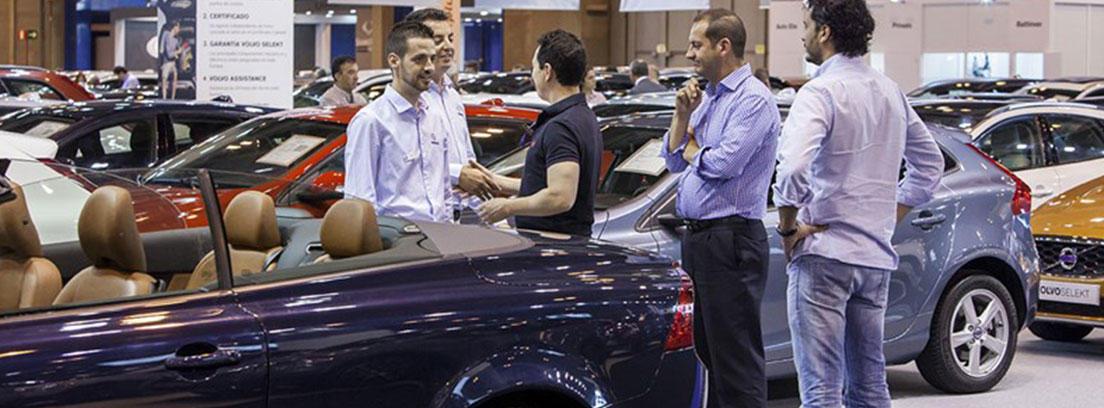 Coche descapotable azul oscuro con varias personas al lado y otros coches