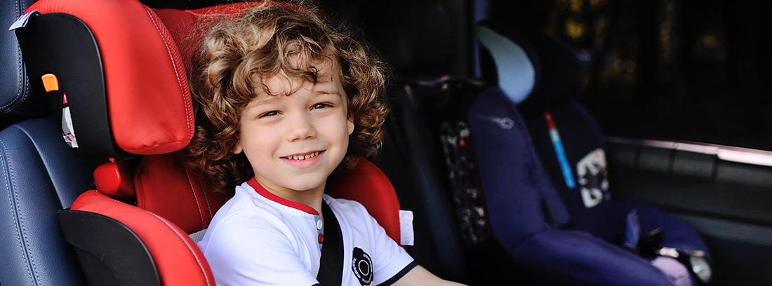 Niño sentado en silla de coche roja con cinturón de seguridad puesto