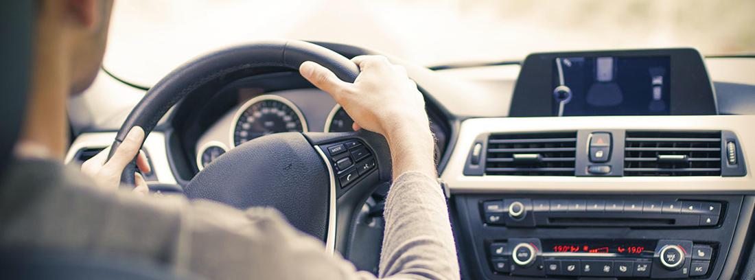 Hombre joven dentro de un coche con las manos en el volante