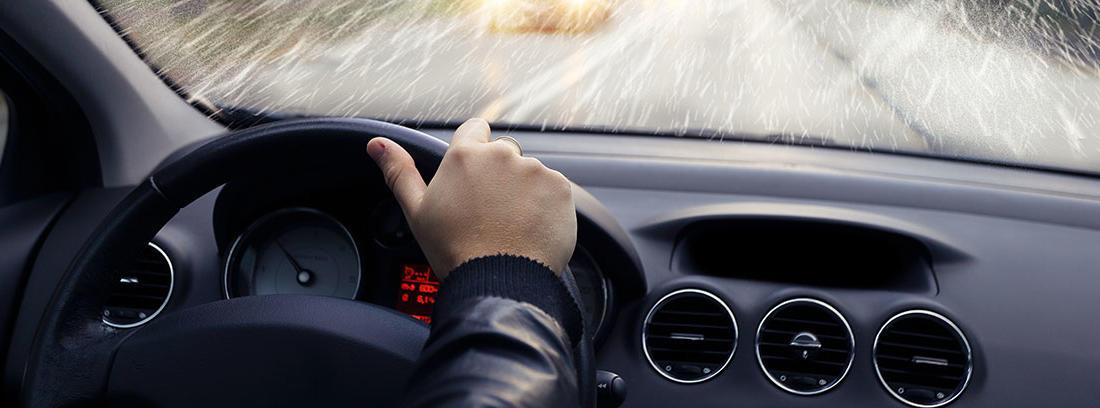 Conductor dentro de un coche en un día lluvioso