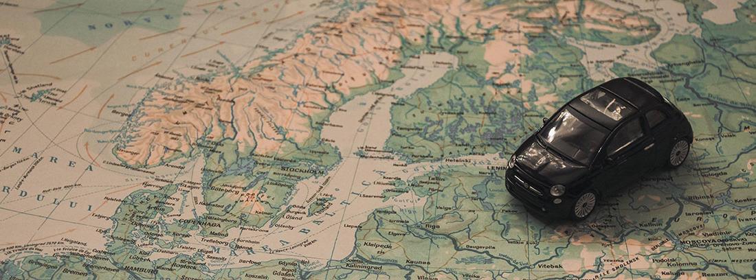 Coche de juguete negro sobre un mapa de Europa