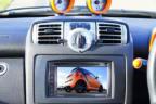 Pantalla central instalada en el salpicadero de un coche junto al volante.
