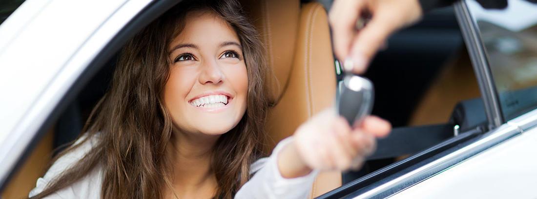 Chica morena, dentro de un vehículo blanco, recibe las llaves de un nuevo coche