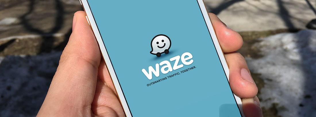 Conductor enseña el móvil con la aplicación Waze abierta en el teléfono.