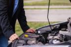 Un hombre revisa el contenido de su coche con el capó levantado.