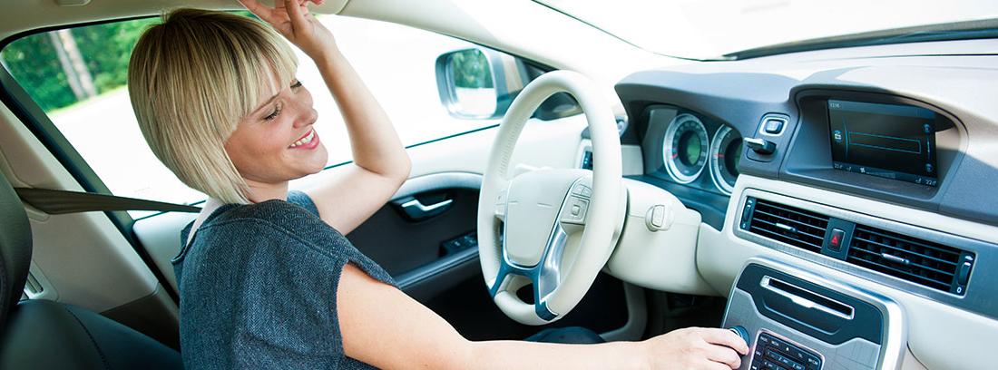 Chica rubia en el habitáculo del conductor sube el volumen de la música bailando.