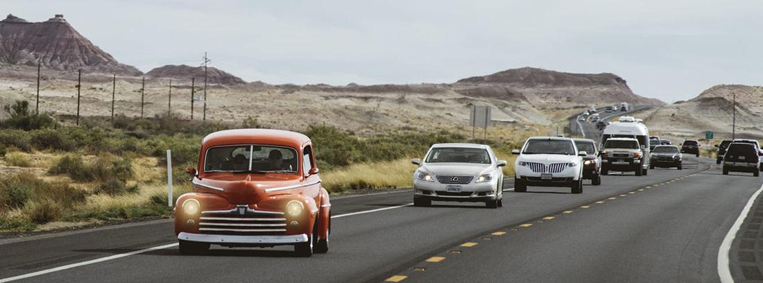 Coche rojo y otros detrás circulando por una carretera.