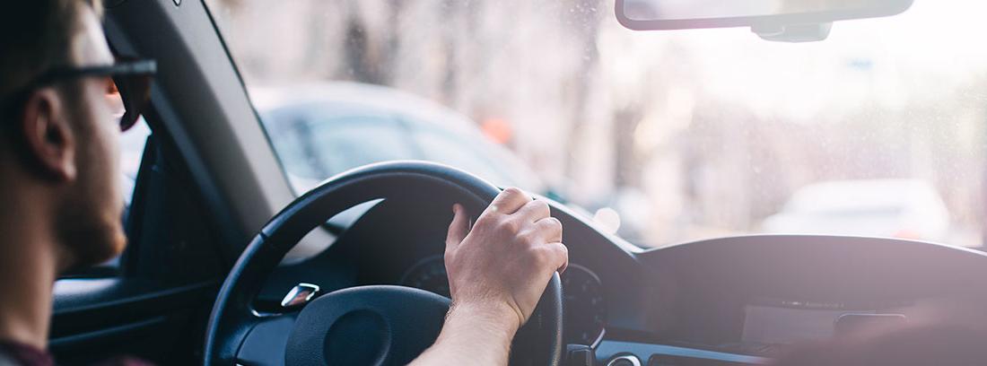 Conductor dentro de un coche con las manos en el volante.