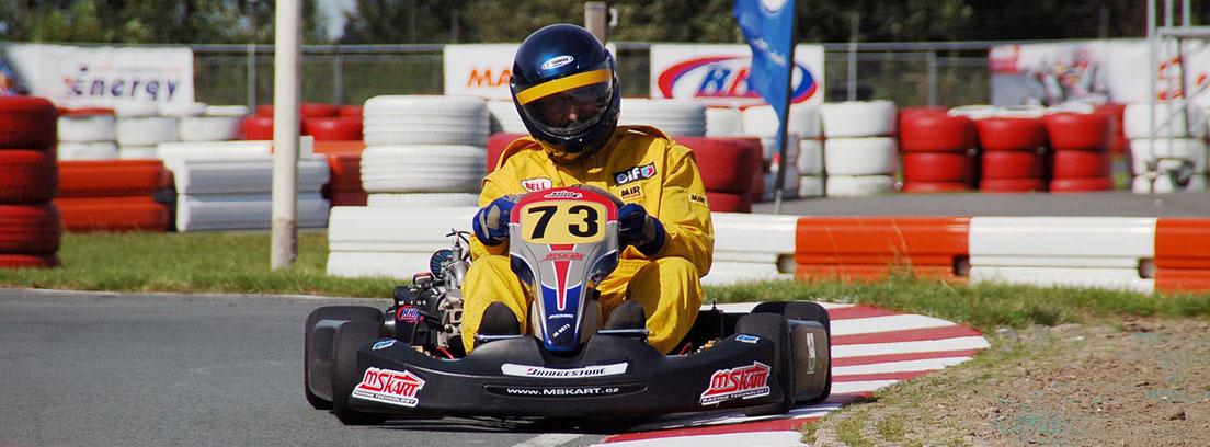 Piloto con mono amarillo y casco negro en un kart con número 73.