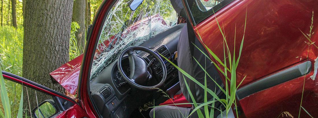 Coche rojo con puerta abierta y cristal delantero roto contra un tronco de árbol.
