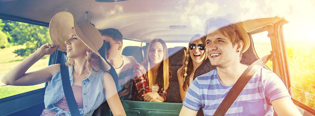 un grupo compuesto por dos chicos y chicas jóvenes sonríen dentro de una furgoneta. Van vestidos con ropa de verano y una de las chicas con una pamela. Miran por una de las ventanillas laterales del vehículo.