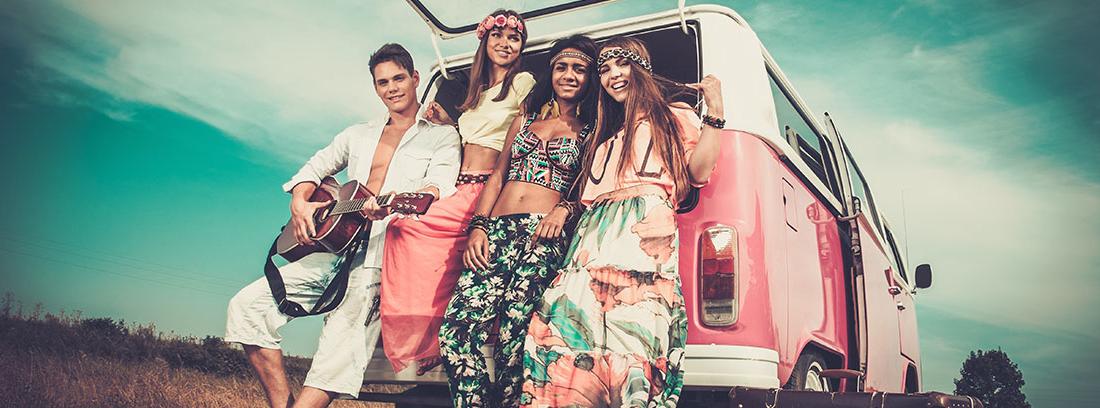 Un grupo de chicos y chicas vestidos con indumentaria hippie se apoyan en el maletero abierto de una furgoneta Wolskvagen rosa. Están sonrientes y el chico sujeta una guitarra. A su lado se encuentran varias maletas.