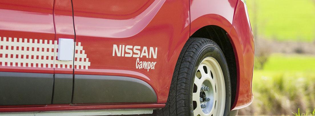 Detalle de la puerta y una rueda de una camper de Nissan