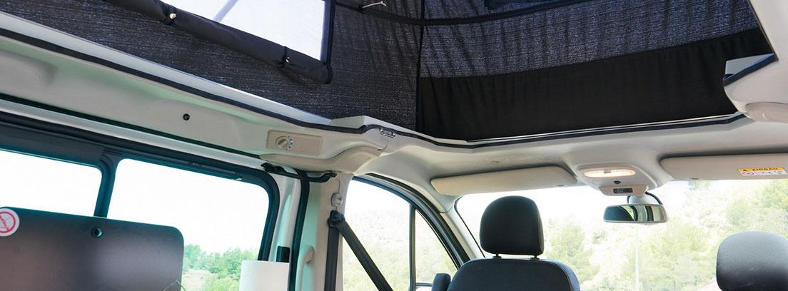 Interior con techo elevado de una camper de Nissan