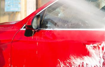 conductor limpiando la puerta de su coche rojo