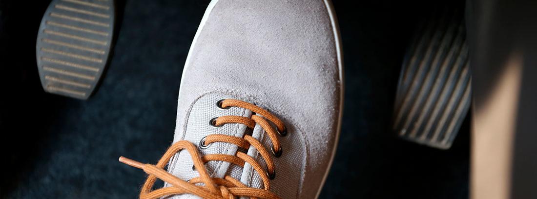 Zapato pisando los pedales de un coche