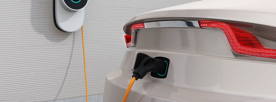 Parte trasera de un vehículo eléctrico de color blanco con toque deportivo cargando a través de un cable.