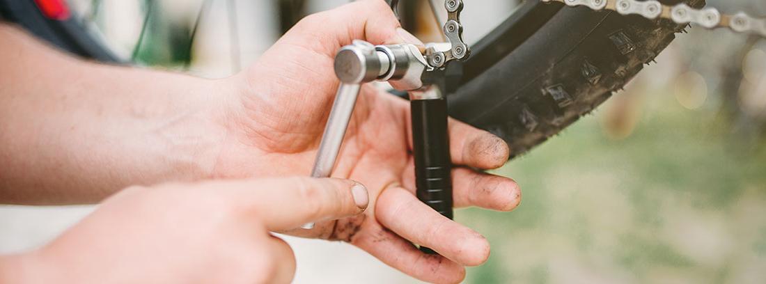 Manos con herramienta sobre una cadena de bici.