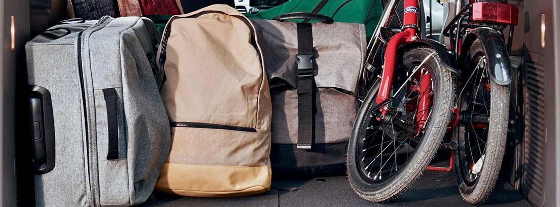Vista interior del Ford Tourneo Connect 2018 desde el maletero, con maletas, mochilas y una bicicleta plegada.