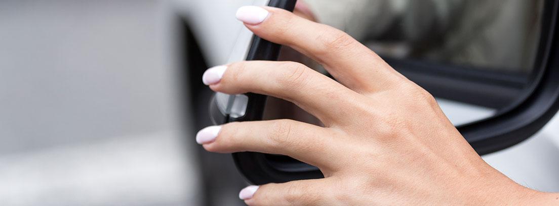 La mano de una mujer ajusta el espejo retrovisor de un coche.