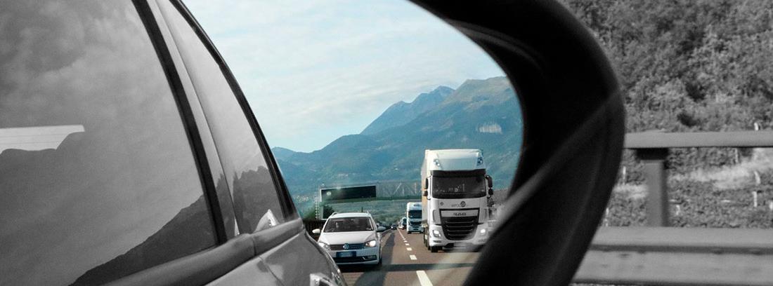 Espejo retrovisor de un coche que muestra un coche y un camión blancos circulando detrás de él