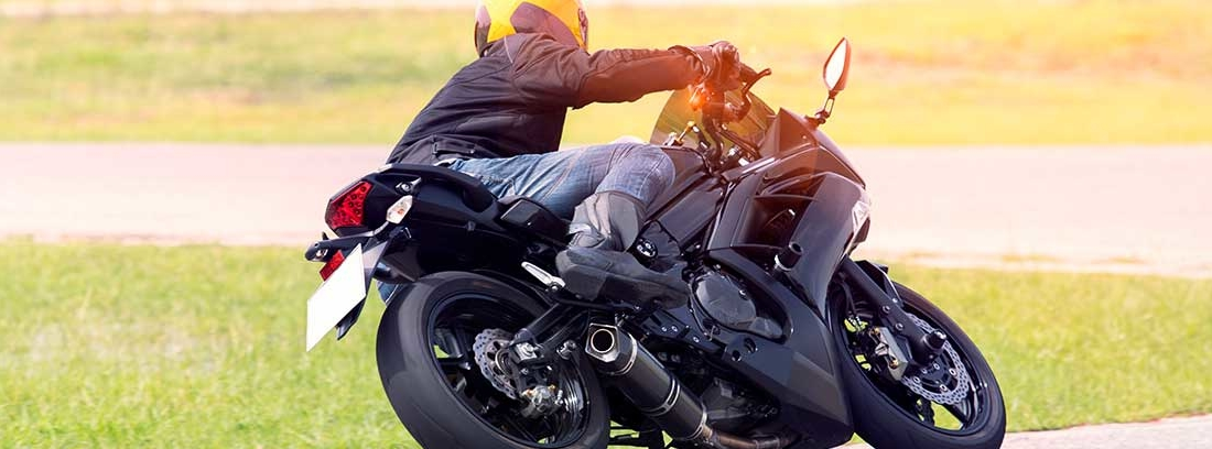 Un hombre conduce una moto. Va inclinado casi por completo al entrar en una curva