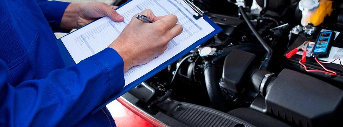 Mecánico apuntando en el libro de mantenimiento de coche