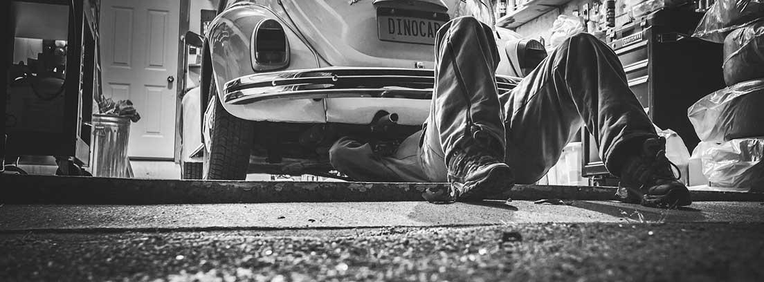 Mecánico arreglando los bajos de un coche