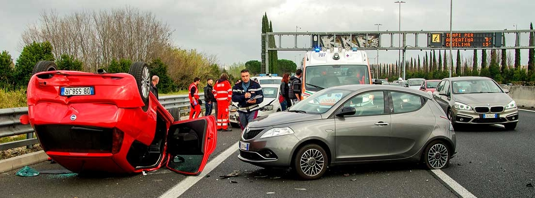 En una carretera un coche rojo volcado y a su lado un coche