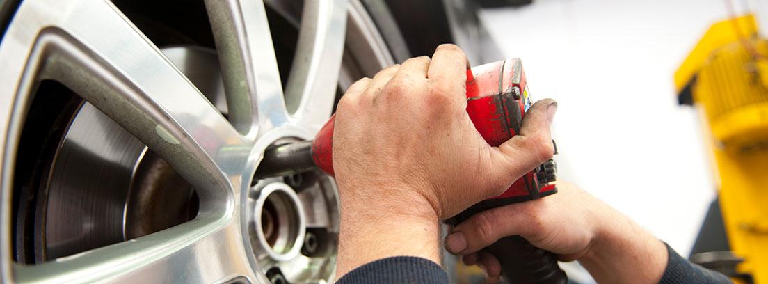 Manos sujetan herramienta sobre llanta de neumático