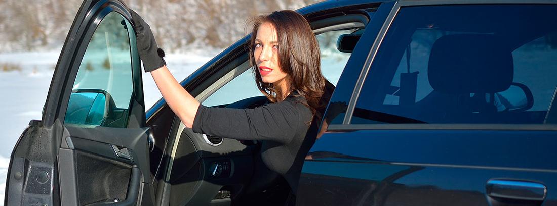 Mujer abriendo la puerta del coche para salir