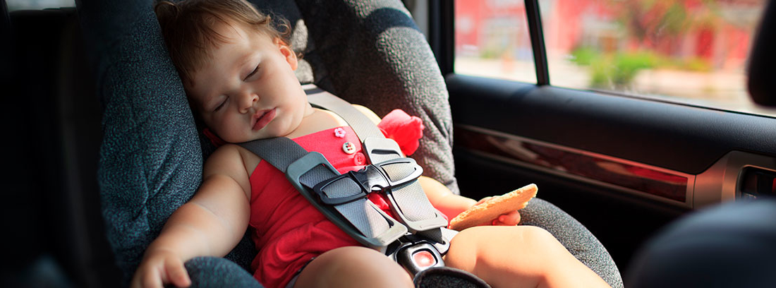 Niño pequeño dormido con arneses puestos en silla de coche
