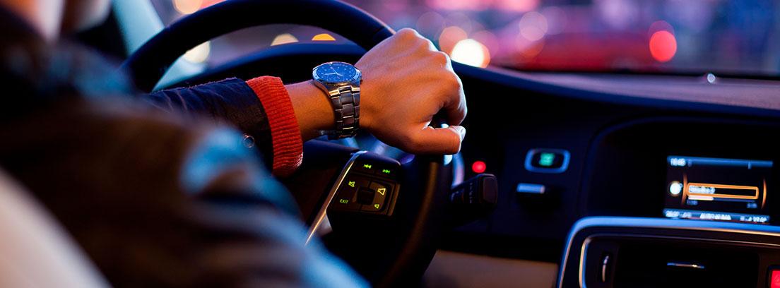 Vista del interior de un coche con una mano sobre el volante