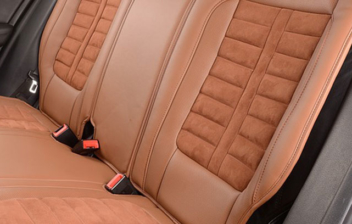 Tapicería mixta de Alcántara y piel marrón en los asientos traseros de un coche