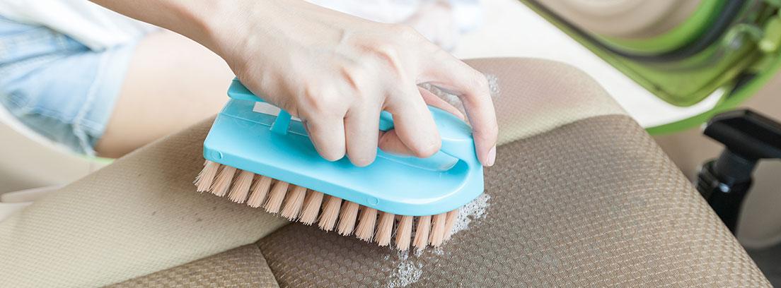 Limpiar con un cepillo azul las manchas de la tapicería de tela de un coche de color gris.