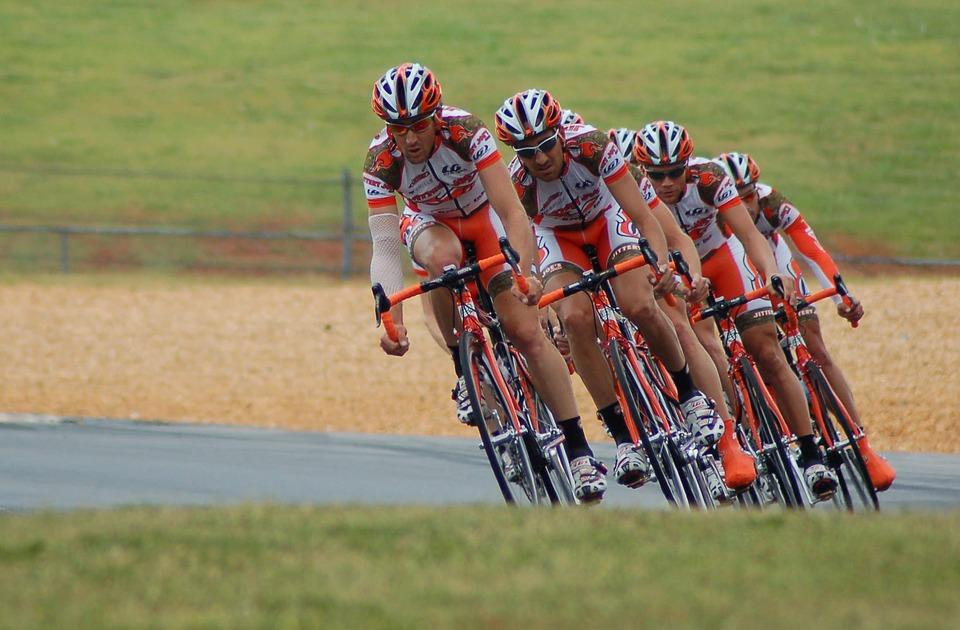 Hilera de ciclistas en carretera con casco y maillot blancos y naranjas.