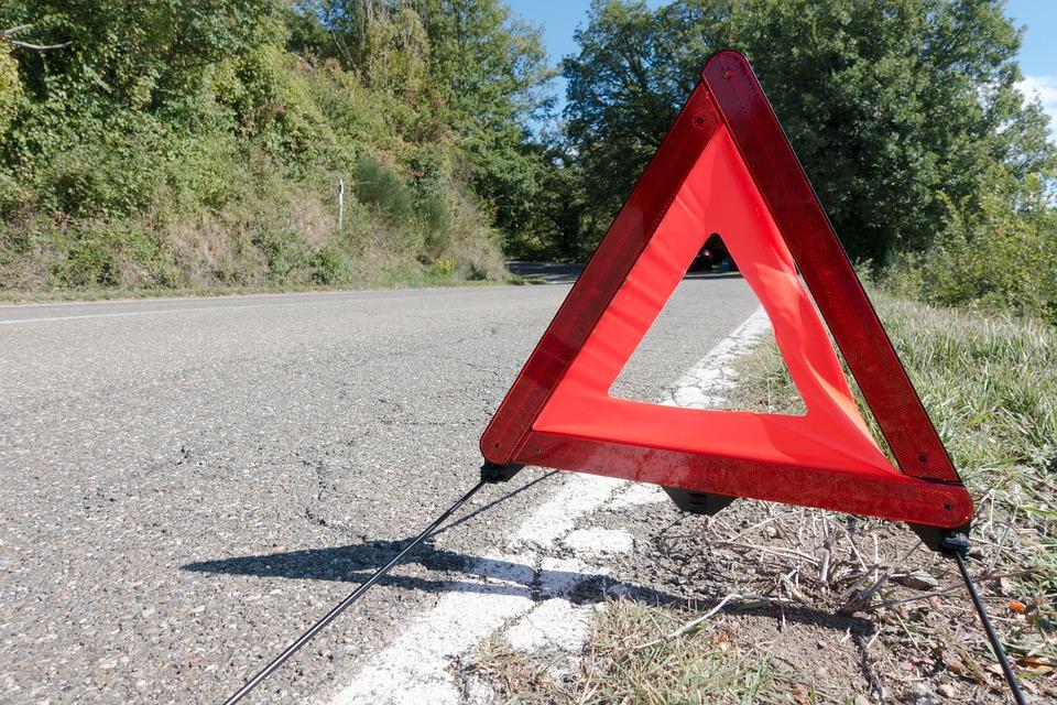 Triangulo rojo de emergencia sobre línea blanca de carretera.