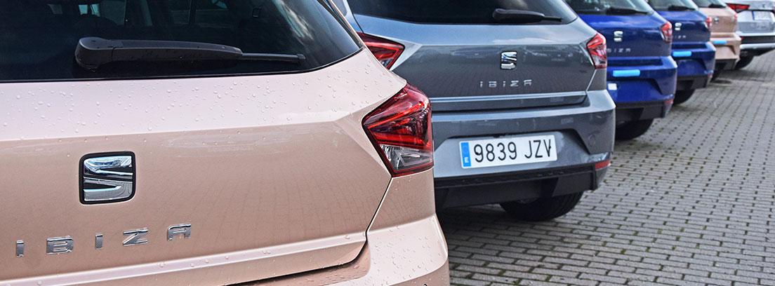 : Imagen trasera de varios Seat Ibiza en gris y azul. Al fondo se ven coches sin matricular.