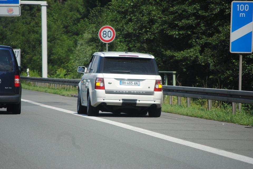 Coche pequeño blanco en arcén de carretera junto línea blanca del margen.
