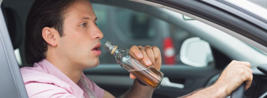 Un hombre bebe mientras conduce