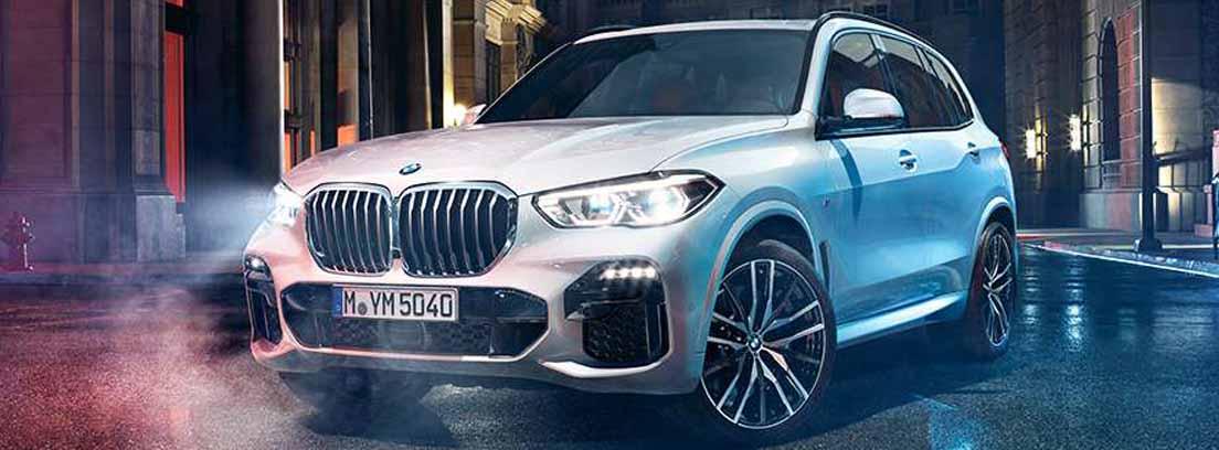 Coche blanco con logo delantero BMW con faros encendidos parado en una calle